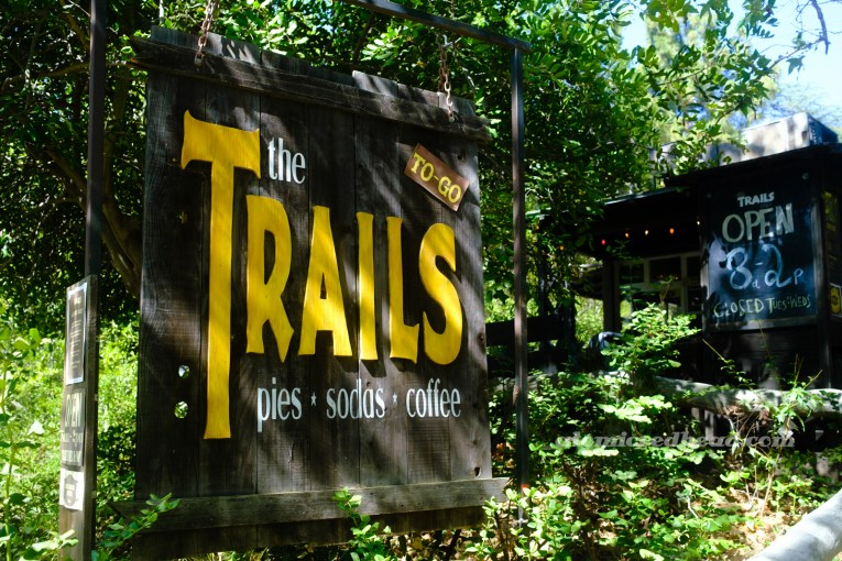 """A large wooden sign reading """"The Trails Pies Sodas Coffee"""""""
