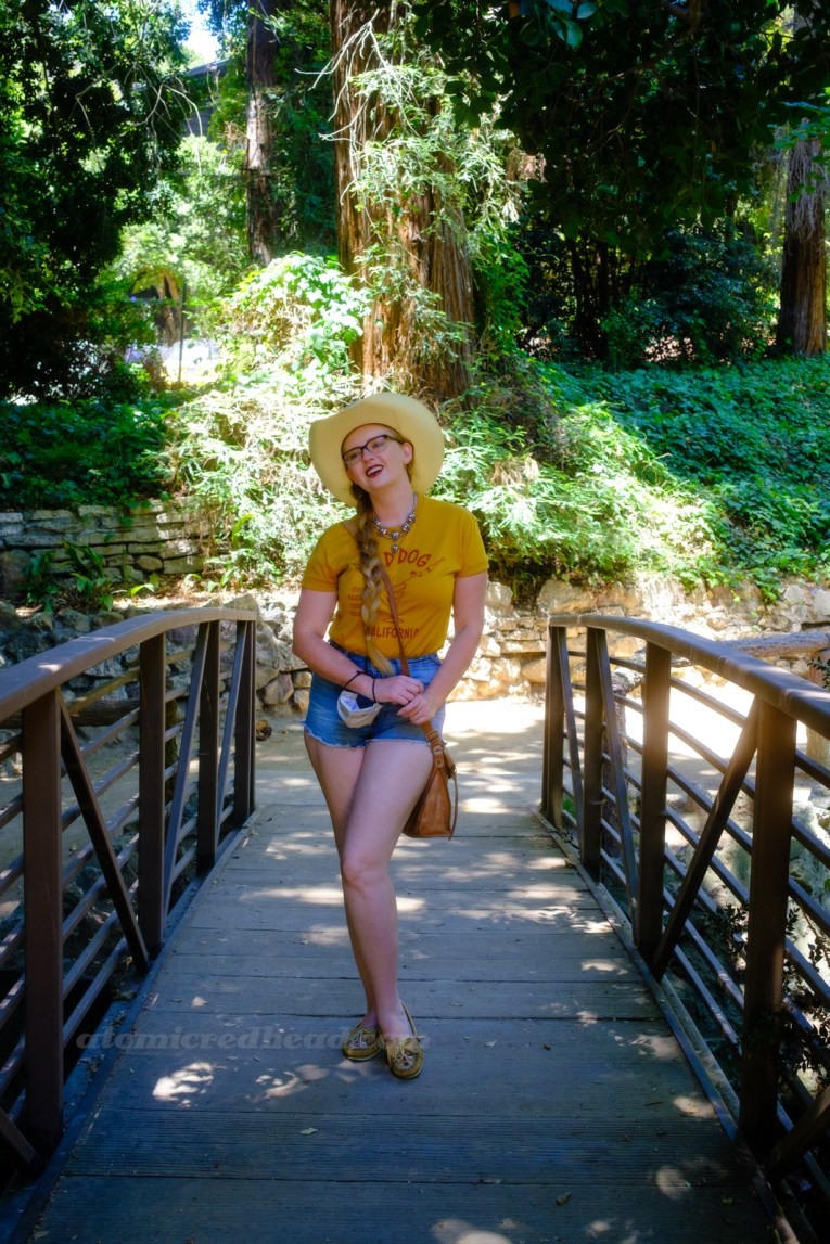 """Myself, wearing a cream straw cowboy hat, yellow shirt red text reading """"Red Dog California Cold Beer Restaurant Cocktails Good Vibes"""" and featuring a woman diving into a martini glass, and jean shorts, standing on a bridge over a small stream."""