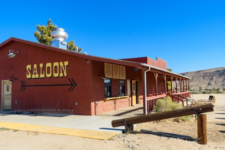 """Exterior back of the Red Dog, a dark red building with a covered porch that has windows facing the outside to pick up food. The back wall reads """"Saloon"""" in yellow letters and features an arrow below."""