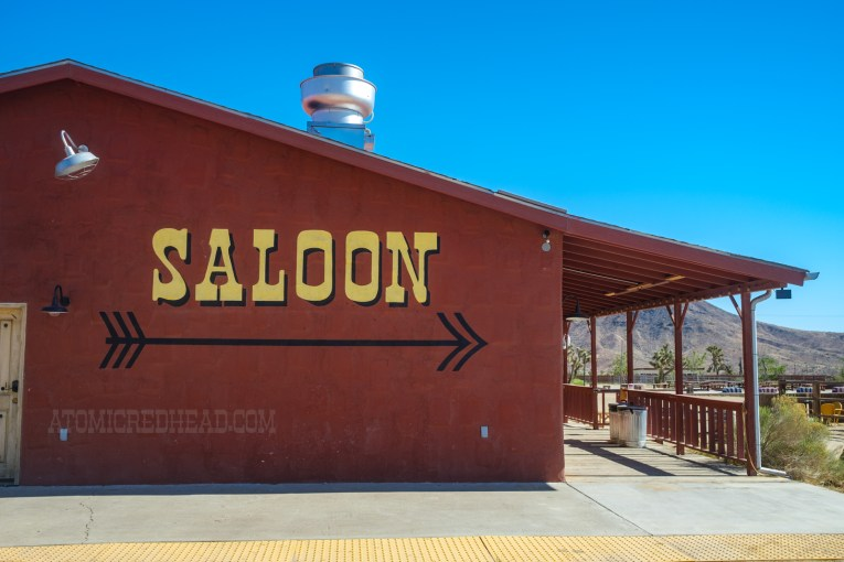 """Back wall of the outside of the Red Dog, large yellow letters reads """"Saloon"""" with a black arrow below."""