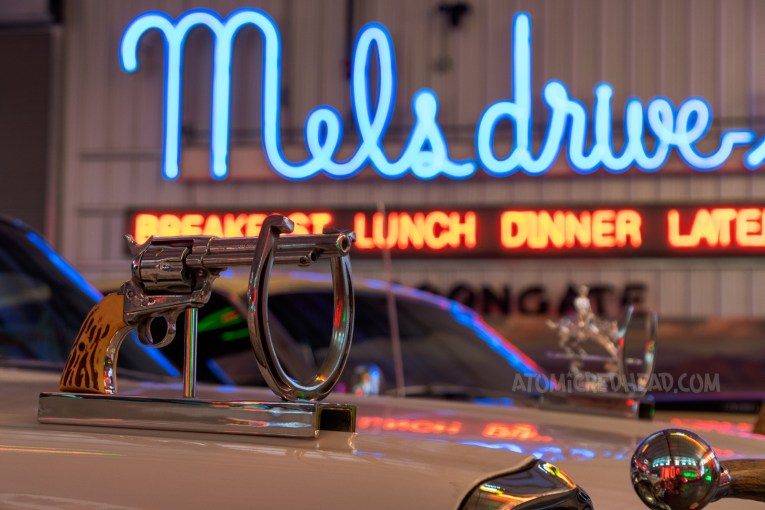 """Close-up of a revolver mounted to the fender of a car, the blue neon of """"Mel's"""" is in the background."""