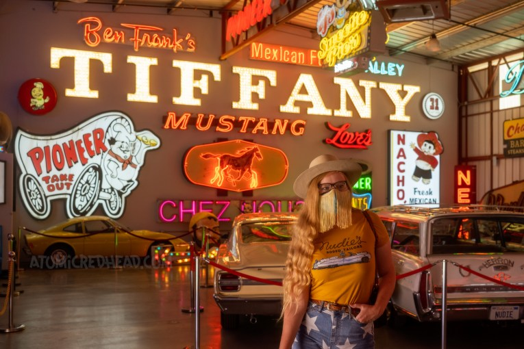 """Myself, wearing a cream cowboy hat, yellow shirt with a large white Cadillac and script reading """"Nudie's Rodeo Tailor"""" and jean shorts with white stars, standing in front of a variety of lit signs."""