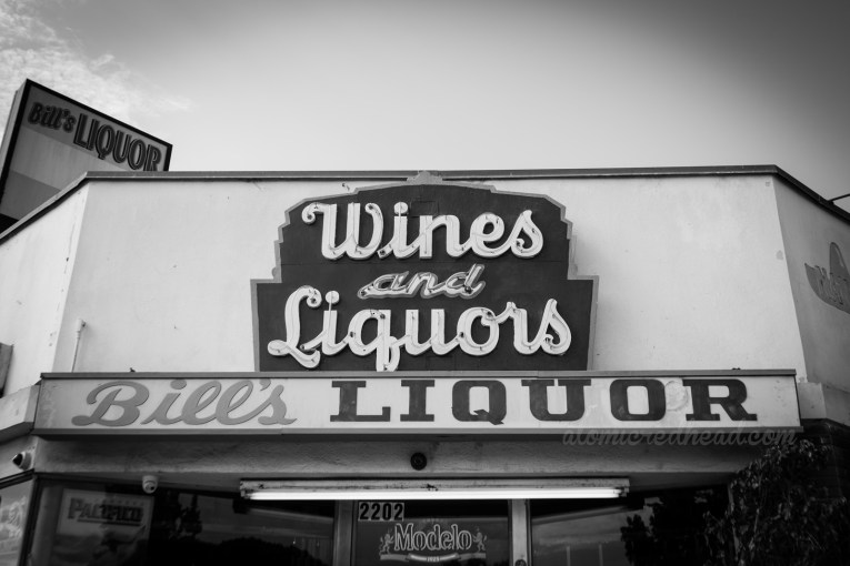 """Black and white photo. A small neon sign reads """"Whites and Liquors"""" in a curving script. Below in backlit plastic reads """"Bill's Liquor"""""""