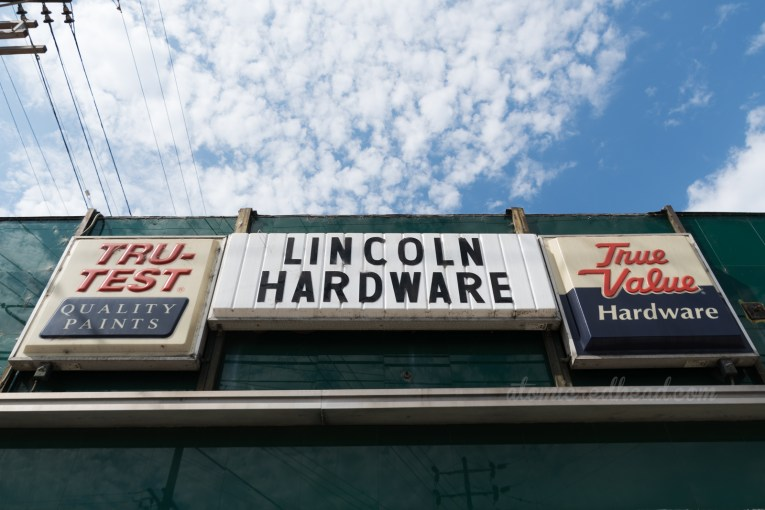 """Three backlit plastic signs read """"Tru-Test Quality Products,"""" """"Lincoln Hardware,"""" and """"True Value Hardware."""""""