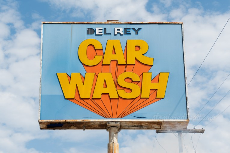"""A blue backlit plastic sign reads """"Del Rey"""" in small letters across the top, and in large 3D style letters of orange reads """"CAR WASH"""""""
