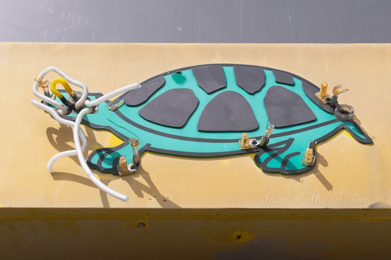 Broken bits of neon hang from a green backlit plastic turtle