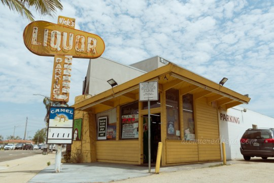 """A yellow building features a yellow and white sign next to it reading """"Nick's Liquor Parking Cigars"""" and features a small arrow."""