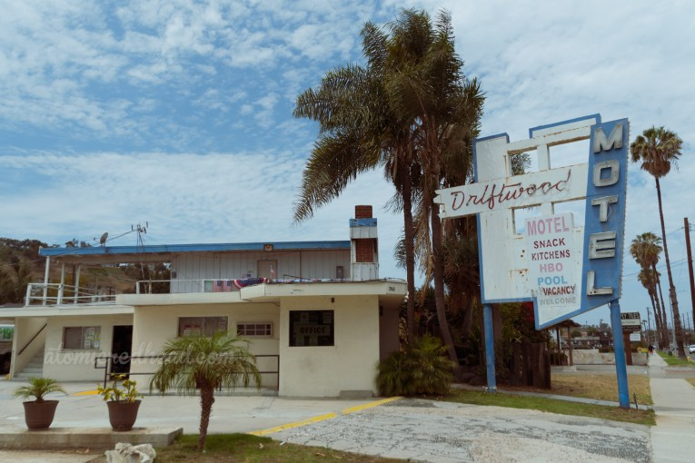 """The Driftwood Motel, a mid-century modern building painted white with blue trim, and features a blue and white sign reading """"Driftwood"""" in red script neon and """"Motel"""" in white letters, painted also on the sign reads """"Snack Kitchens, HBO, Pool, Welcome"""" and also features a small """"No Vacancy"""" neon."""