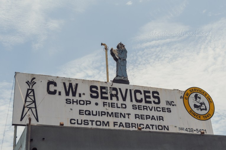 """A large white sin reads """"C.W. Service Shop Field Services Equipment Repair Custom Fabrication Since 1945"""" and atop it features a man in coveralls welding a pipe, all made of neon."""