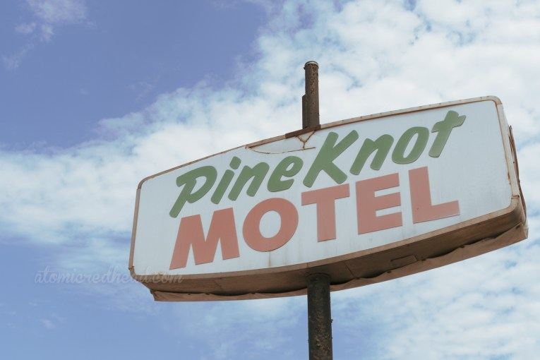 """A white backlit plastic sign reads """"Pine Knot Motel"""" in green and red letters."""