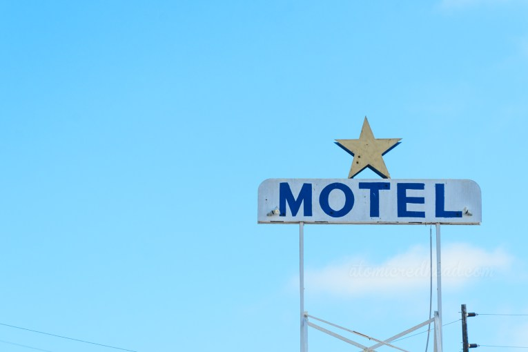 """A small white sign pokes into a blue sky, the white sign reads 'MOTEL"""" in blue letters and features a gold painted star on top."""
