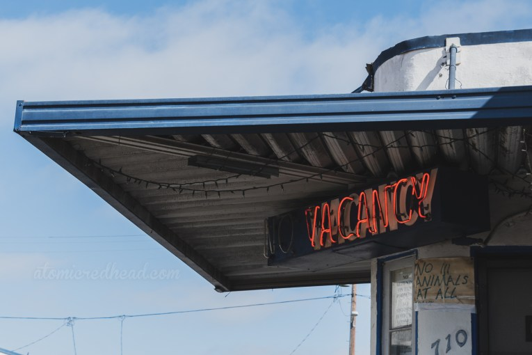 """Close-up of the """"No Vacancy"""" neon above the office window."""