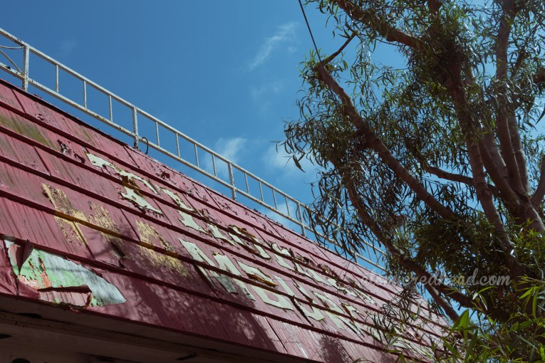 """Flaking yellow paint reads """"Thomas Hamburgers"""" on a red roof."""