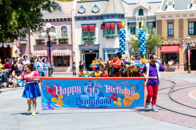 """A small parade celebrating Disneyland's 66th birthday, two Cast Members carry a large blue banner that reads """"Happy 66th Birthday, Disneyland"""" behind them is a vintage firetruck carrying Mickey Mouse and features two massive candles made of balloons."""