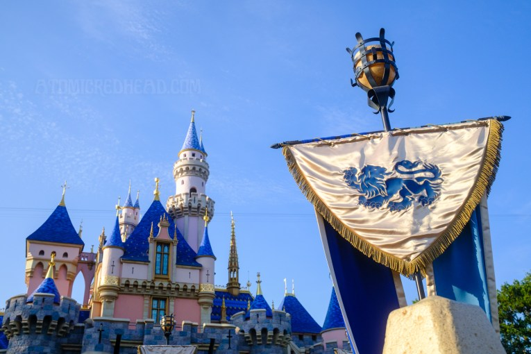 Painted in bright shades of pink and blue sits Sleeping Beauty Castle against a blue sky.