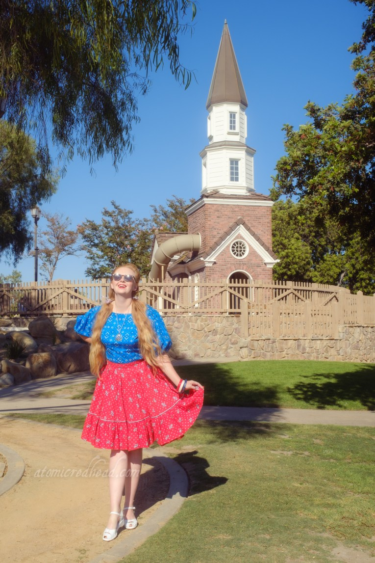 """Myself, wearing a blue peasant top with a bandana print on it, a red skirt with """"76"""" in white scattered throughout, and white shoes, standing in front of a small replica of the Old North Church."""