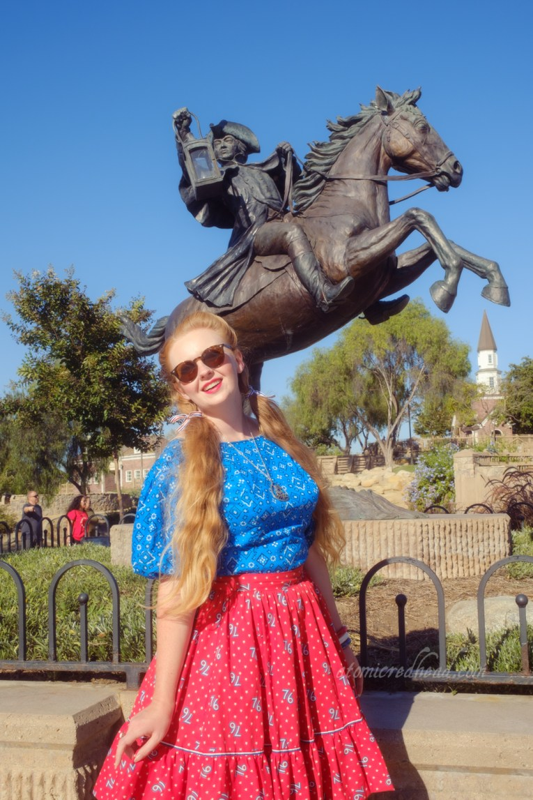 """Myself, wearing a blue peasant top with a bandana print on it, a red skirt with """"76"""" in white scattered throughout, and white shoes, standing in front of a statue of Paul Revere, holding a lantern and sitting atop a rearing horse."""