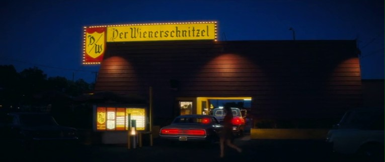 Der Wienerschnitzel as it appears in Once Upon a Time in Hollywood, lit up at night with a red roof and yellow sign.