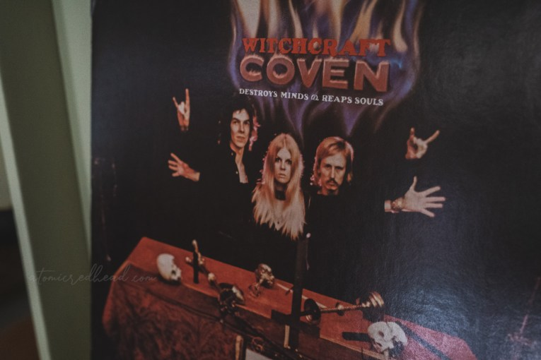 """The back of the album, features the band members, the blonde in the middle, with her hands spread wide, the men on either side, each raising one hand with the """"sign of the horns"""" in front of them in an alter covered with a red tablecloth and features items such as a skull, chalice, and dagger."""