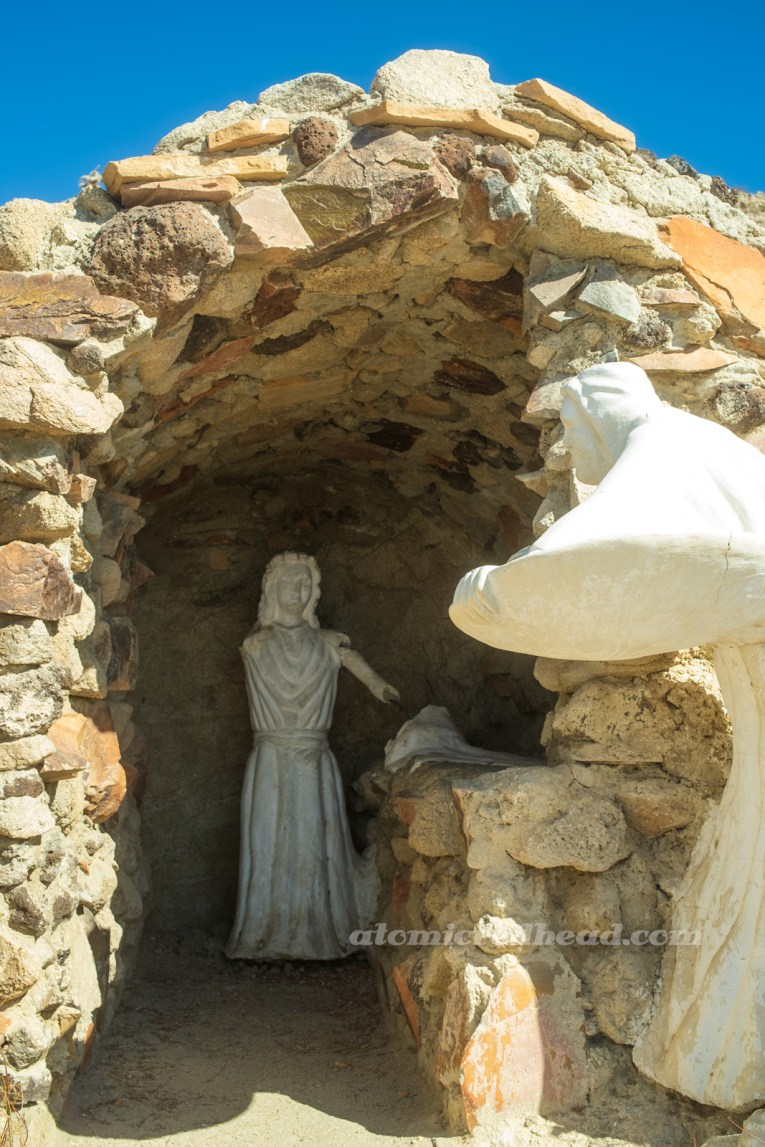 A small statue, that has broken parts of its arm over the years, sits within a small cave.