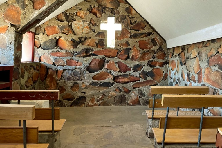 Inside the small stone church. The back wall features the warm, brown and orange rocks, with a small window shaped like a cross in the center. Wood benches flank the edges.