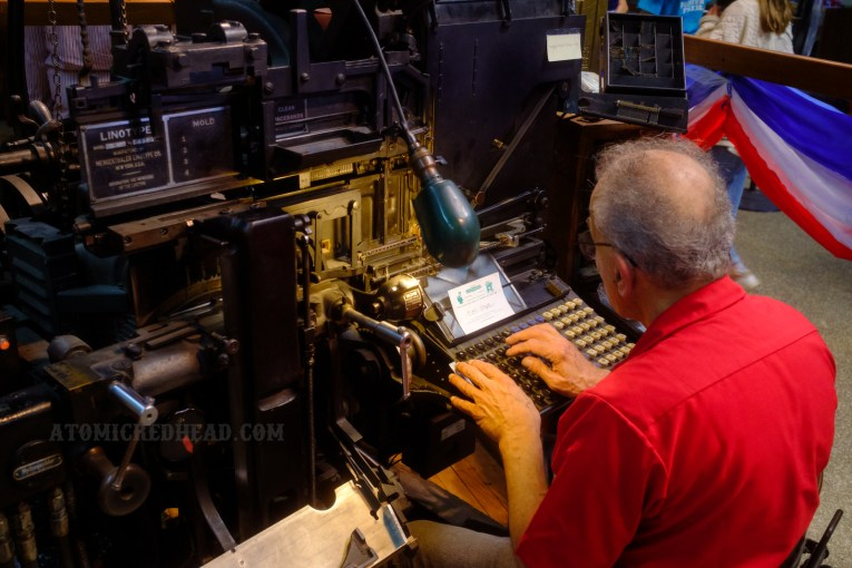 A man sits at a Linotype machine making Linotype stamps.