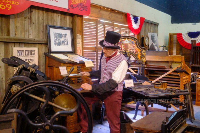 A man demonstrates how one of the antique printing presses is used.