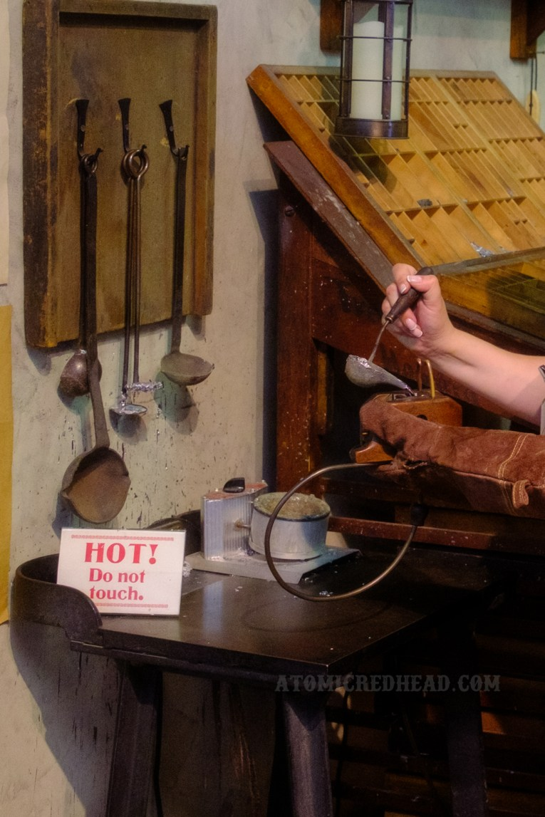 A woman demonstrates how letter press letters are made, by pouring hot metal into a mold.