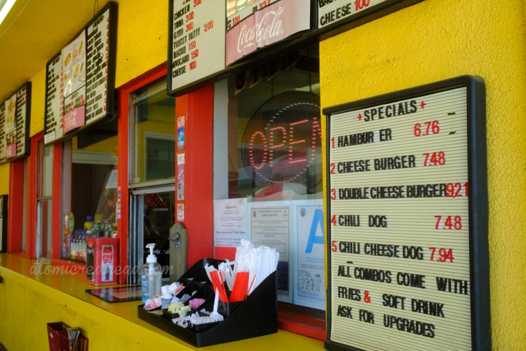 """The order window is trimmed in red and sit within a bright yellow building. A small menu board to the right of the order window reads """"Specials Hamburger Cheeseburger Double Cheeseburger Chili Dogs Chili Cheese Dog All Combos Come with Frights & Soft Tree Ask for Upgrades."""