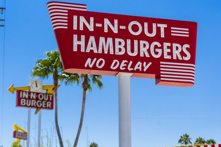 """In the foreground is the replica of the original sign reading """"In-N-Out Hamburgers No Delay"""" just beyond it is a later sign, featuring a yellow arrow and red rectangle reading """"In N Out Burger"""" with a clock in the middle of the arrow, all of which features neon. And beyond that sign is the newest sign, red with a yellow arrow, reading """"In N Out Burgers"""" but made of backlit plastic."""