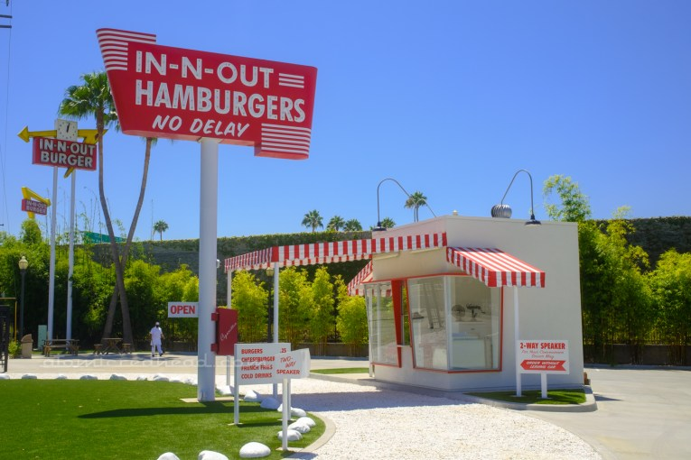"""Replica of the first In-N-Out, a small, ten foot by ten foot white box, with red and white stripe awnings, a white rock horseshoe driveway curves up to the building. Just before the window is a small white box with red letters reading """"Two-Way Speaker"""" another sign to the right reads """"2-Way Speaker For Your Convenience Driver May Order without Leaving Car."""" A tall sign to the left reads """"In-N-Out Hamburger No Delay"""" in neon."""
