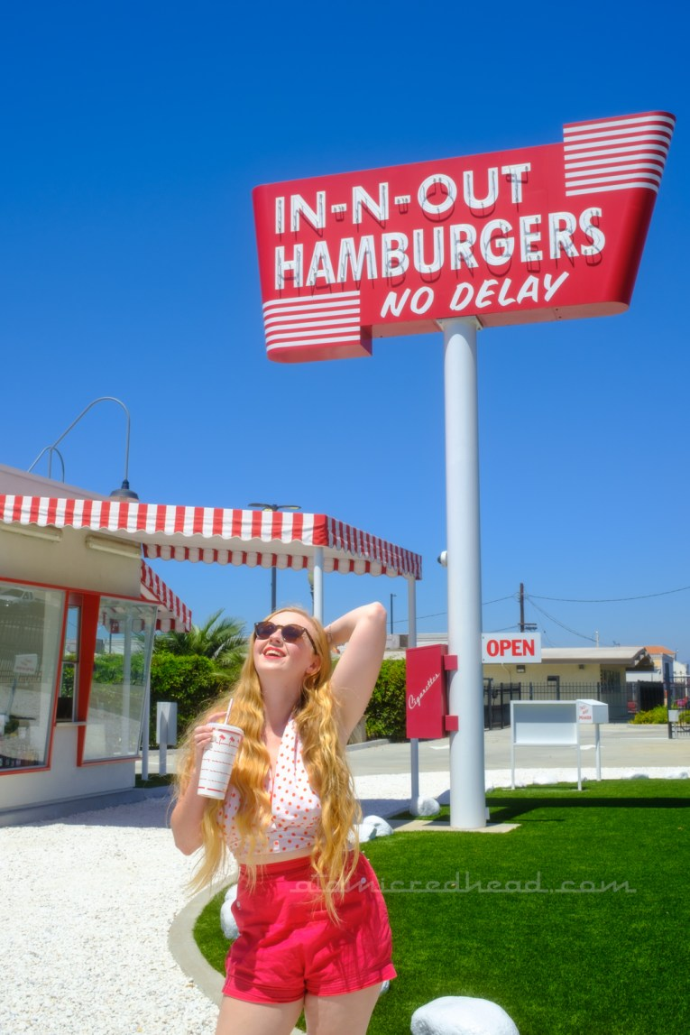 Myself, wearing a white halter top with red polka dots, and red shorts, holding a red and white In-N-Out cup, standing in front of the replica of the first In-N-Out.