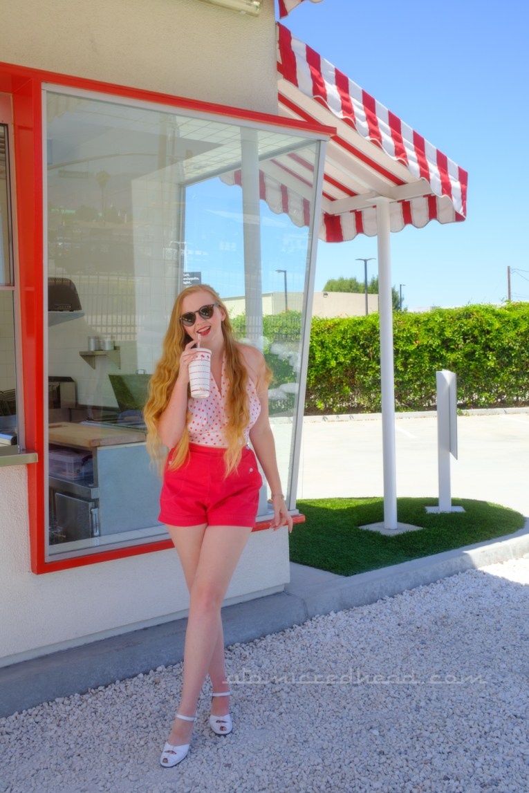 Myself, wearing a white halter top with red polka dots, and red shorts, holding a red and white In-N-Out cup, standing under the awning near the window of the In-N-Out.