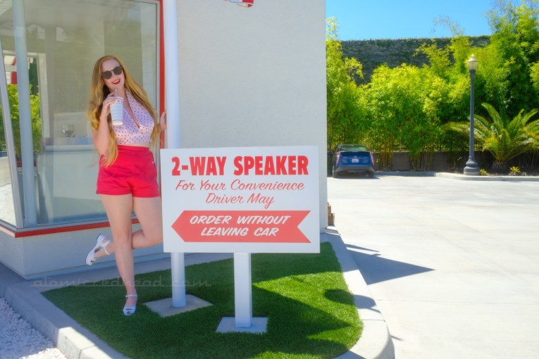 """Myself, wearing a white halter top with red polka dots, and red shorts, holding a red and white In-N-Out cup, standing next to a white sign reading """"2-Way Speaker. For Your Convenience Driver may Order without Leaving Car"""" in red letters."""