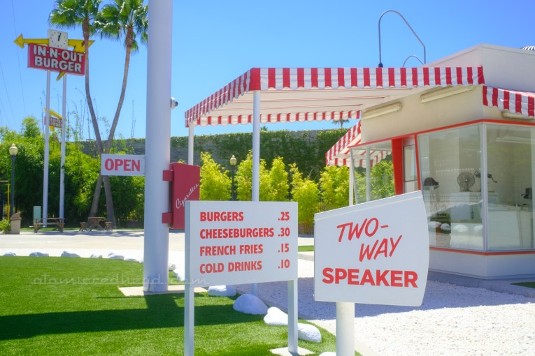 """A white box reading """"Two-Way Speaker"""" on it in red letters sits in the foreground, just beyond it is the menu board, reading """"Burgers .25 Cheeseburgers .30 French Fries .15 Cold Drinks .10"""" in red letters, and just beyond it sits the replica building with a red and white stripe awning over the pick-up window."""