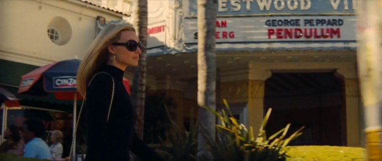 Margo Robbie as Sharon Tate walks was the Fox Westwood Village Theater, the neon marquee visible in the background.