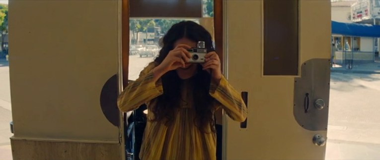 The ticket girl holds up a camera outside the ticket booth to take a picture of Robbie as Tate.
