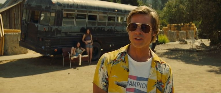 Cliff, dressed in a yellow shirt with an Asian landscape print on it over a white Champion Spark-plugs t-shirt, a school bus behind him sits in front of the remains of the old Corriganville stables.