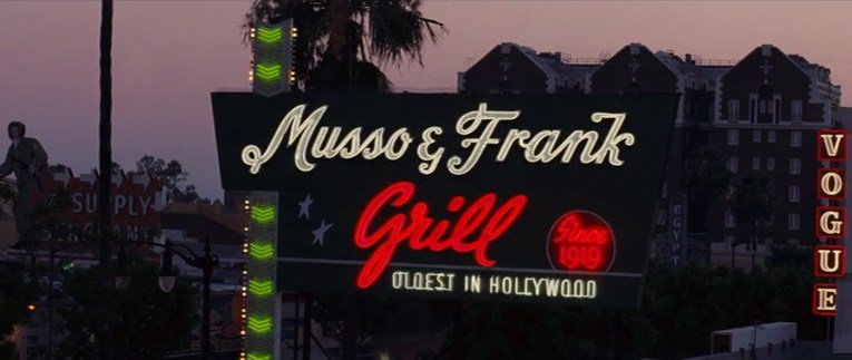 """Musso & Frank Grill sign as it appears in Once Upon a Time...In Hollywood, lit up at night, a massive green sign with neon script reading """"Muss & Frank"""" in white, """"Grill Since 1919"""" in red, and small text reading """"Oldest In Hollywood"""" in white neon."""