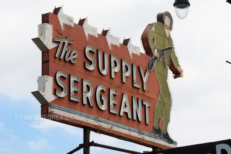 """The Supply Sergeant as it appears today, during the daytime, with a massive told neon soldier on the right, and text reading """"The Supply Sergeant"""" in white letters."""
