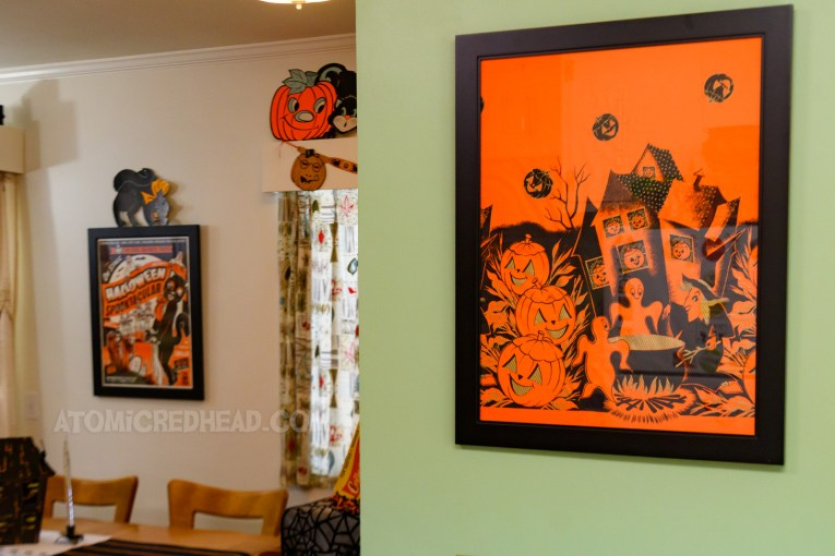 """View from the kitchen looking into the dining room. On the right is a green painted wall with a framed piece of vintage table cloth with a witch and ghost, in the dining room a framed poster for Bob Baker's """"Halloween Spooktacular"""""""