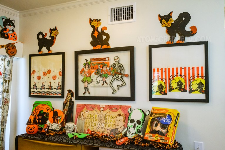 The back wall of dining room. On the wall are three frames, the left features a piece of vintage paper tablecloth, with Jack O'lanterns and witches, the middle piece is a witch and skeleton with a guitar, the right piece is also a piece of vintage paper tablecloth with images of a haunted house. Sitting atop the three frames are three black cat die cuts. Below, atop the secretary are various Halloween decorations, including a die cut of a haunted house, skeleton dressed as a pirate, and skull, a small blow mold Jack O'lantern, a ceramic skull mug, a spirit board, and a pirate costume in the box.