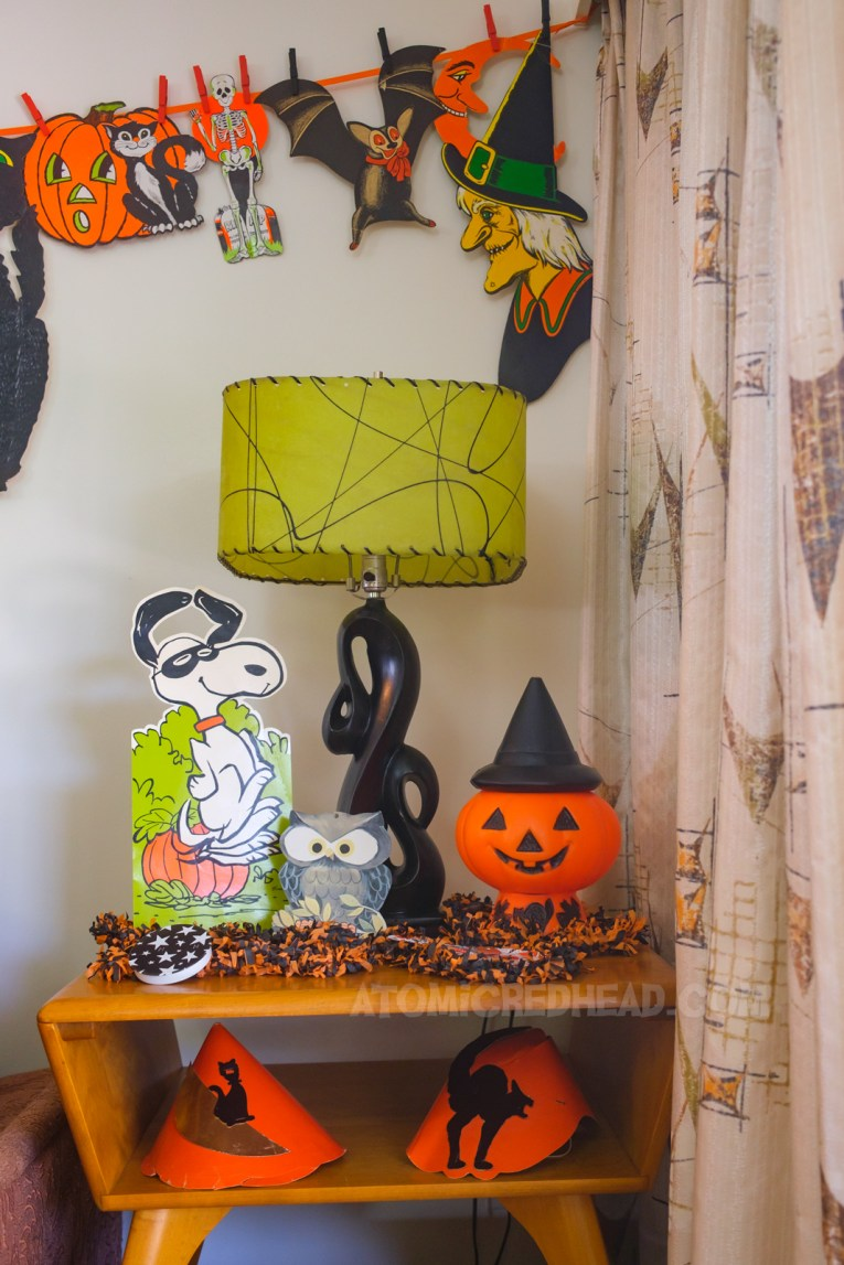 A small table sits next to curtains, on it is a black lamp with a green shade, a small cardboard standup of Snoopy dancing, wearing a mask, in a pumpkin patch, a small die cut of an owl, and a blow mold Jack O'lantern wearing a witch hat.
