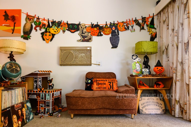 Overall view of part of our living room, featuring a 50s chair, table with a lamp, Snoopy cardboard cut out, and blow mold Jack O'lantern with a witch hat atop it, above both is a garland of various Halloween die cuts, including pumpkins, back cats, bats, skeletons, and witches.