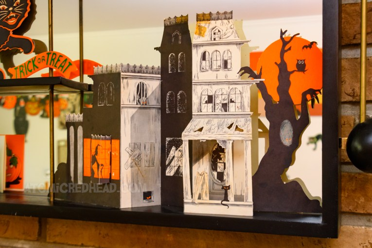 A large die cut of a haunted house, with a black cat on the porch, and a witch in the window.