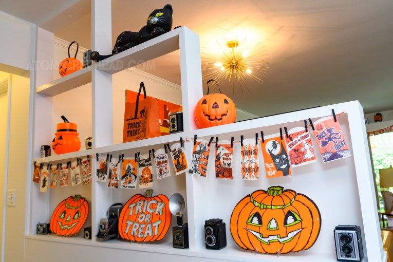 A partially open room divider separates our living room from our hallway, within it is a garland made of many small trick or treat bags, three die cut Jack O'lanterns, and various blow mold Jack O'lanterns.