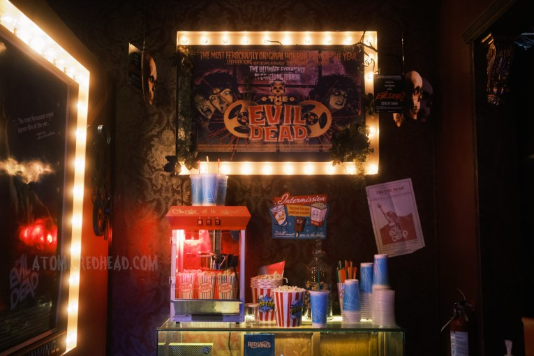 """A faux movie concessions stand, featuring popcorn maker, and sodas. Above is a post for the Evil Dead reading """"'The most ferociously original horror film of the year' -Stephen King Best selling author of The Shining and Carie. The Ultimate Experience in Grueling Terror The Evil Dead."""""""