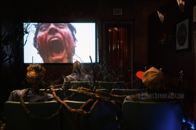 A small mock-up cinema, featuring skeletons seated in seats with vines growing around, the screen is showing clips of the Evil Dead trilogy.