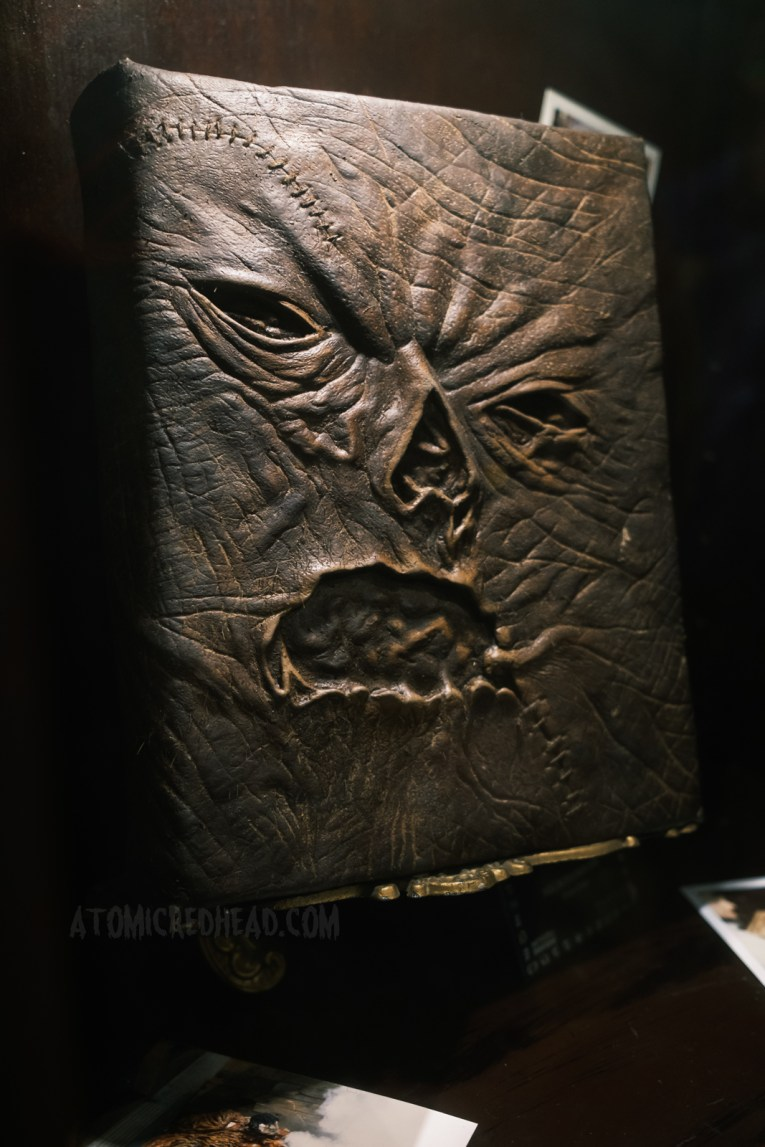 """Screen used version of the Necronimicon, a book """"bound in human flesh"""" features a warped human face."""