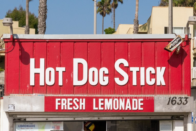 """Close-up of the front of the building, reading """"Hot Dog Stick Fresh Lemonade"""" in white letters."""